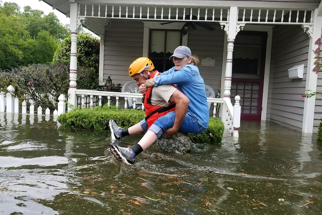 A Texas National Guardsman carry's a resident's from her home affected by flooding.