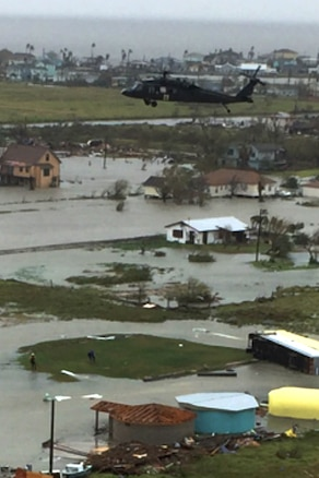 An Army UH-60 Black Hawk helicopter hovers over flooded buildings.