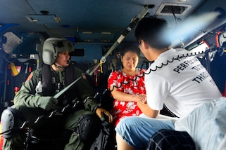 Coast Guardsmen interact with people in a helicopter.