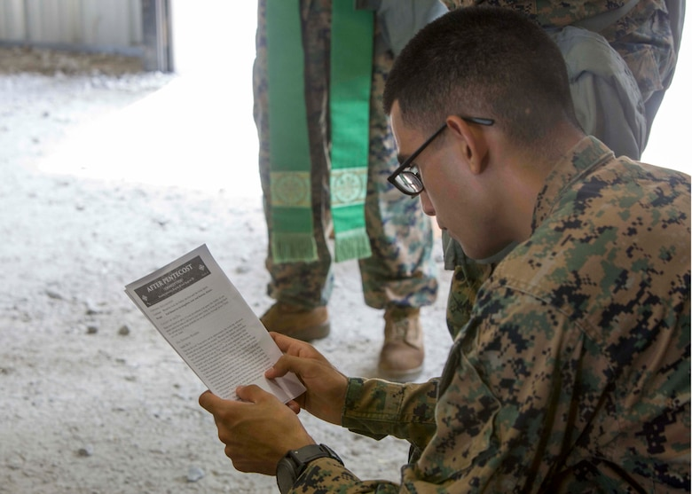U.S. Marine Corps Sgt. Mitchell Sanchez, a legal service specialist with the 26th Marine Expeditionary Unit (MEU), reads a sermon as part of religious services during Realistic Urban Training at Camp Davis Training Area, N.C., Aug. 20, 2017.