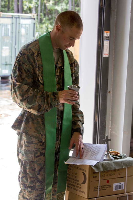 U.S. Navy Lt. Cmdr. John M. Mabus, the 26th Marine Expeditionary Unit (MEU) chaplain, prepares to give communion at a religious service during Realistic Urban Training (RUT) at Camp Davis Training Area, N.C., Aug. 20, 2017.
