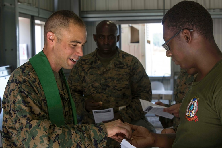 U.S. Navy Lt. Cmdr. John M. Mabus, the 26th Marine Expeditionary Unit (MEU) chaplain, passes out bread for communion to Marines during realistic urban training (RUT) at Camp Davis Training Area, N.C., Aug. 20, 2017.
