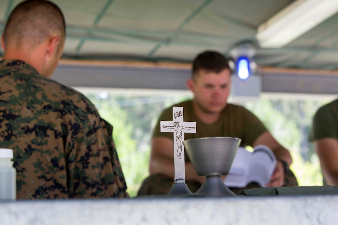 U.S. Navy Lt. Cmdr. John M. Mabus, the 26th Marine Expeditionary Unit (MEU) chaplain, reads a sermon to Marines as part of religious services during Realistic Urban Training (RUT) at Camp Lejeune , N.C., Aug. 20, 2017.