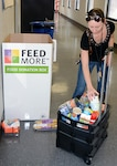 Jami Zanetta loads canned foods into a cart to take to Feedmore.