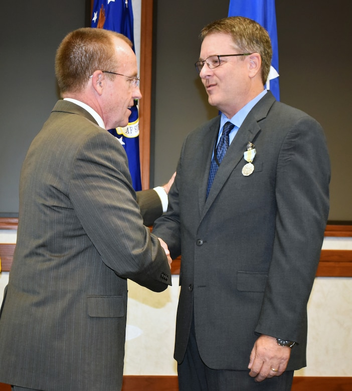 Jeffrey Allen, Air Force Sustainment Center executive director, congratulates Steven Alsup on receiving the Meritorious Civilian Service Award during a farewell ceremony for the AFSC Logistics Director Aug. 25 in the Anaconda Conference Room, Bldg. 3001.
