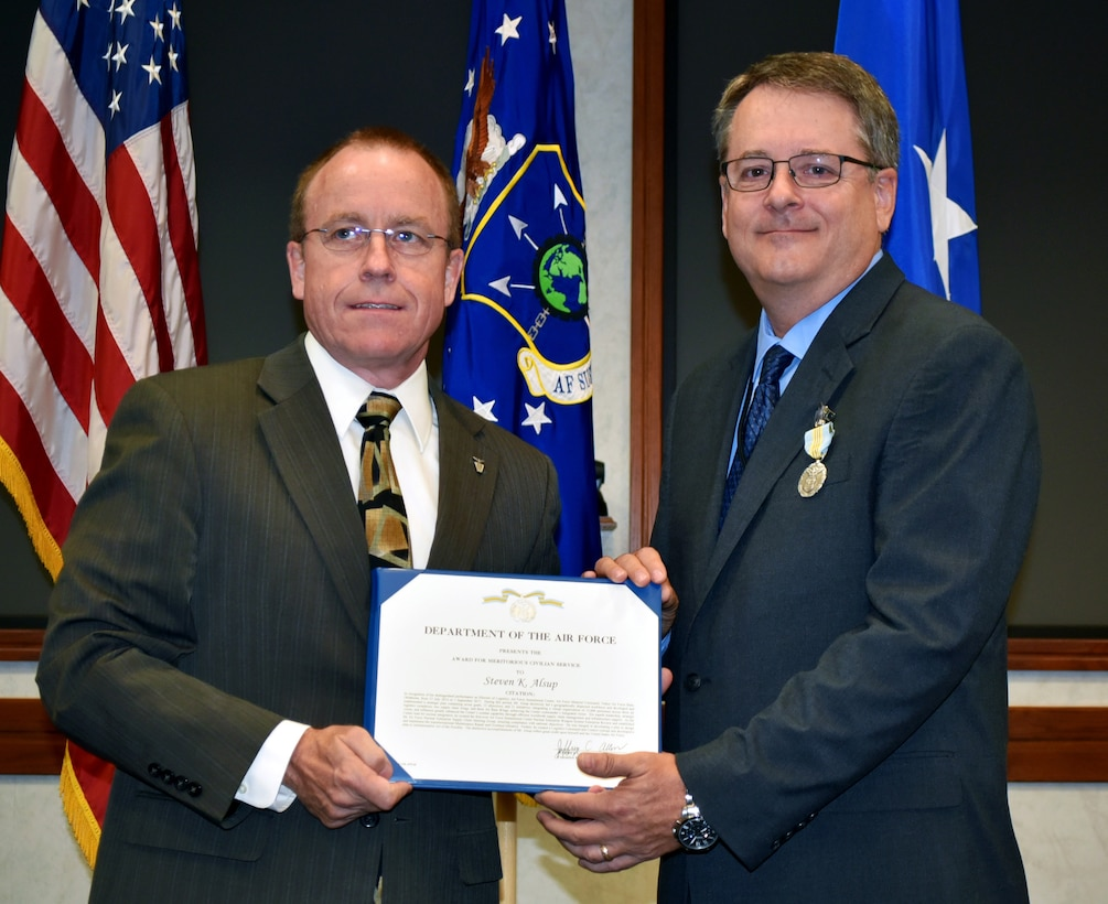 Jeffrey Allen, Air Force Sustainment Center executive director, presents Steven Alsup with the Meritorious Civilian Service Award during a farewell ceremony for the AFSC Logistics Director on Friday in the Anaconda Conference Room, Bldg. 3001.