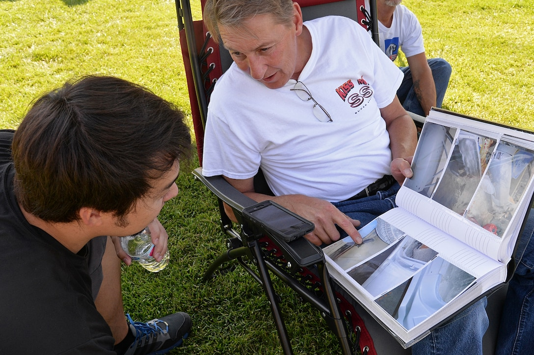Curtis Welter, Ogden ALC quality assurance, takes a moment to show off pictures and talk about his 1971 El Camino SS during the annual Ogden Air Logistics Complex summer picnic and car show. (U.S. Air Force photo by Alex R. Lloyd)