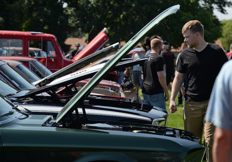 An enthusiast looks at all the horsepower being displayed under the hoods, during the annual Ogden Air Logistics Complex summer picnic and car show. (U.S. Air Force photo by Alex R. Lloyd)