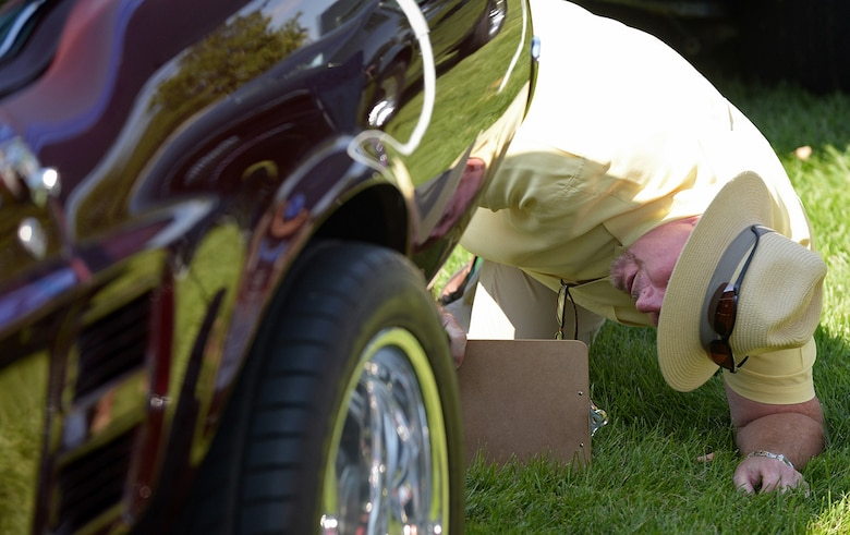 Douglas James, Ogden Air Logistics Complex, inspects a classic Ford Mustang while judging the vehicles assembled during the annual Ogden Air Logistics Complex car show. (U.S. Air Force photo by Alex R. Lloyd)