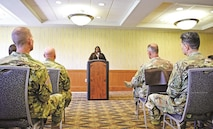 Darlene Washington, retired sergeant first class and ombudsman for Regional Health Command-Center, speaks to an audience of Soldiers and civilians during the Women's Equality Day observance Aug. 16 at Riley's Conference Center.