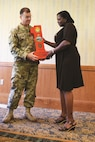 Col. Ronald Black, left, commander of 1st Combat Aviation Brigade, 1st Infantry Division, presents a Big Red One to Darlene Washington, retired sergeant first class and ombudsman for Regional Health Command-Center, as an award for her service as guest speaker during the Women's Equality Day observance Aug. 16 at Riley's Conference Center.