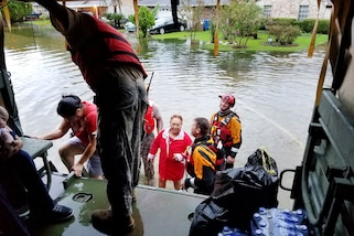Texas Army National Guardsmen help residents affected by flooding caused by Hurricane Harvey board a military vehicle