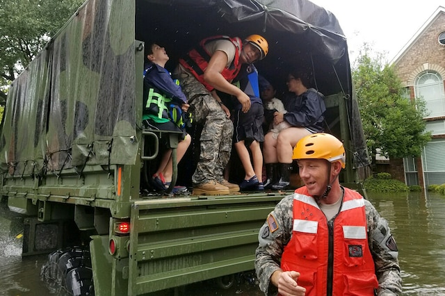 Guardsmen help residents affected by flooding caused by Hurricane Harvey.