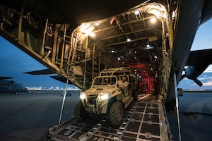A military vehicle drives out of the rear of a military aircraft.