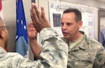 Airman in fatigues with hand raise to give oath, facing half-left as USAF officer administers oath.