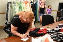 Kimberly Jones fills out a form to borrow a dress from the Cinderella's Closet program, Aug. 23, 2017, at Seymour Johnson Air Force Base, North Carolina.