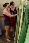 Katie Everett (left), and Cameron Stripling browse through the selection of evening gowns at the Cinderella's Closet program, Aug. 23, 2017, at Seymour Johnson Air Force Base, North Carolina.