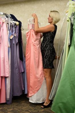 Kristina Balboa, Cinderella's Closet organizer, re-racks a gown at the Cinderella's Closet program, Aug. 23, 2017, at Seymour Johnson Air Force Base, North Carolina.