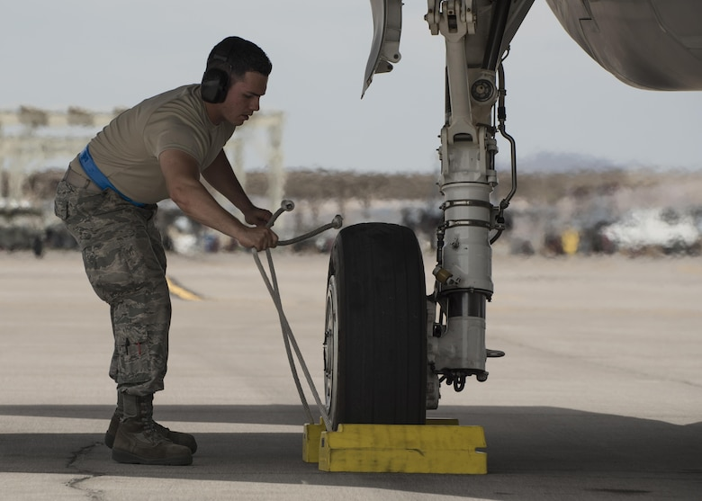 Staff Sgt. Marcos Cruz La Santa, 33rd Aircraft Maintenance Squadron avionics systems technician, pulls chocks from beneath an F-35A Lightning II July 18, 2017, at Nellis Air Force Base, Nev. Cruz is one of the first core F-35 trained maintainers in the Air Force to become a noncommissioned officer. (U.S. Air Force photo by Staff Sgt. Peter Thompson)