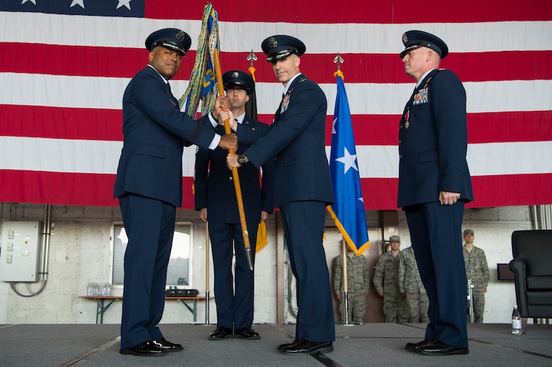U.S. Air Force Lt. Gen. Richard Clark, 3rd Air Force commander, passes the 52nd Fighter Wing guidon to Col. Jason Bailey, incoming 52nd Fighter Wing commander, during the wing change of command ceremony in Hangar 1 at Spangdahlem Air Base, Germany, Aug. 29, 2017. During the ceremony Col. Joseph McFall relinquished command of the 52nd FW after two and half years as the commander of five groups, 24 squadrons, 11 geographically separated units spread across five countries with 5,000 dedicated military and civilian personnel. (U.S. Air Force photo by Senior Airman Dawn M. Weber)
