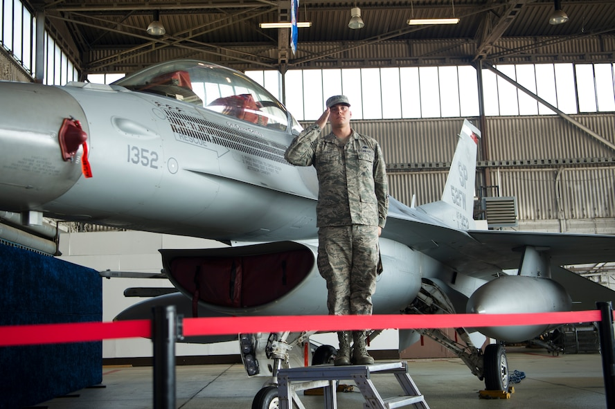 U.S. Air Force Staff Sgt. Eric Gerke, 52nd Aircraft Maintenance Squadron dedicated crew chief unveils the name of Col. Jason Bailey, incoming 52nd Fighter Wing commander, on the wing's flagship F-16 Fighting Falcon fighter aircraft during the wing change of command ceremony in Hangar 1 at Spangdahlem Air Base, Germany, Aug. 29, 2017. Bailey took command of the wing after serving as commander of the 455th Expeditionary Operations Group, Bagram Air Field, Afghanistan. (U.S. Air Force photo by Senior Airman Dawn M. Weber)