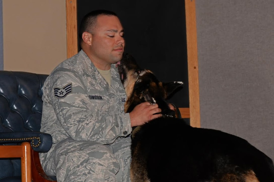 Staff Sgt. Cody Davidson, 47th Military Working Dogs patrolman, sits with his K-9 partner Foxo during Foxo's retirement ceremony at Laughlin Air Force Base, Texas on August 25, 2017.