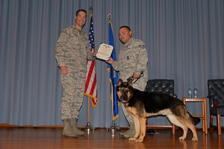 U.S. Air Force Maj. Matthew McGinnis, 47th Security Forces Squadron commander, presents an award to Staff Sgt. Cody Davidson, 47th Military Working Dogs patrolman, and his K-9 dog Foxo, during a retirement ceremony for Foxo at Laughlin Air Force base, Texas on August 25, 2017.