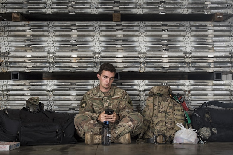 Senior Airman Fife, 723d Aircraft Maintenance Unit, sits against a wall of aircraft pallets in a staging hanger, Aug. 26, 2017, at Naval Air Station Fort Worth Joint Reserve Base, Texas.