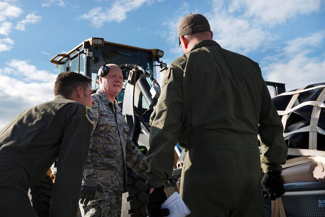 Airmen load and secure cargo onto large machinery.