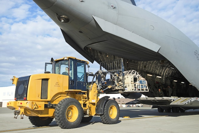 An airman uses a heavy forklift to load cargo and equipment onto a plane.