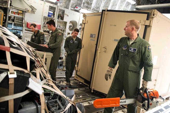 A group of Airmen load equipment in the cargo hold of an airplane.