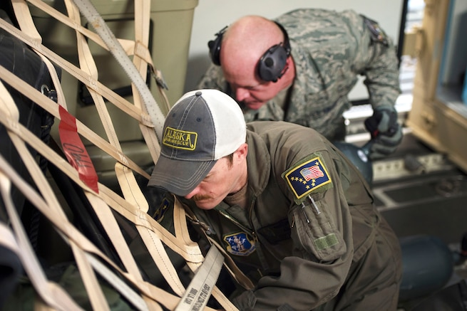 Airmen load and secure cargo onto an airplane.
