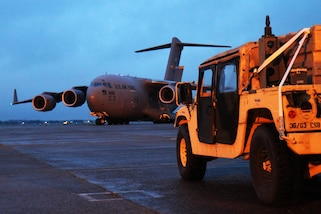 Military equipment sits on a runway.
