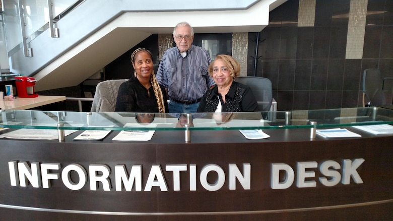Ms. Marjorie Dixson, left, Mr. Ron Liljedahl, center, and Ms. Bettye Wray are volunteers at Malcolm Grow Medical Clinic and Surgery Center.  They work at the main information desk in building 1060, helping to direct patients to clinics and answering questions.