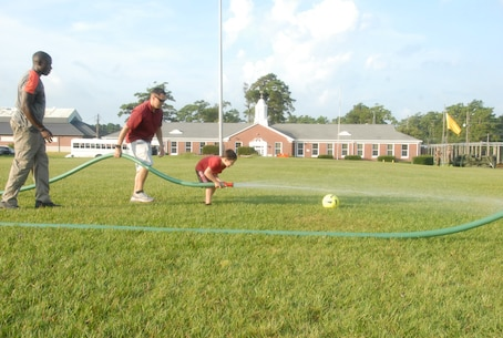 On 18 August, 2017 MCES held its annual Kids Rock Day. Throughout the day parents and children participated in engineer, utilities, and Marine themed activities which showcased their parents' contribution to MCES. One event challenged children to score a goal using water from a hose.  Staff Sergeant David Hackman assists his son across Ellis Field to score a goal.