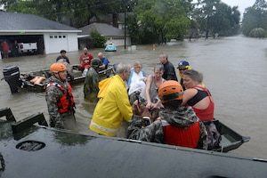 A group of guardsmen and first responders help people into a boat in floodwaters.