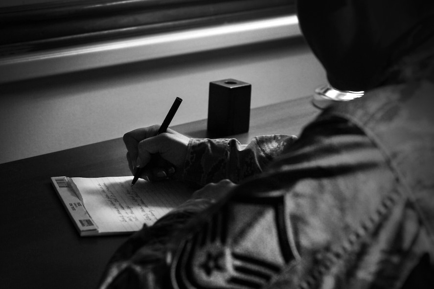 A photo depiction of a master sergeant writing poems with pen and paper. Master Sgt. Zhyronn Carter, 373rd Intelligence, Surveillance and Reconnaissance Group/Alaska Mission Operations Center, Joint Base Elmendorf-Richardson, Alaska, recently published her book in November 2016. According to Carter, her book consists of poems about domestic abuse and sexual trauma from different points of views. (U.S. Air Force photo/Staff Sgt. Alexandre Montes)