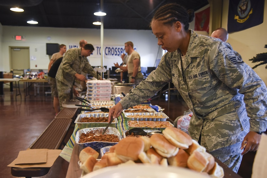 U.S. Air Force Staff Sgt. Cecile King, 315th Training Squadron instructor, lays out food for the Airmen dorm dinner at the Crossroads on Goodfellow Air Force Base, Texas, Aug. 25, 2017. The dinner showed appreciation for Airmen and was free of charge. (U.S. Air Force photo by Airman 1st Class Chase Sousa/Released)