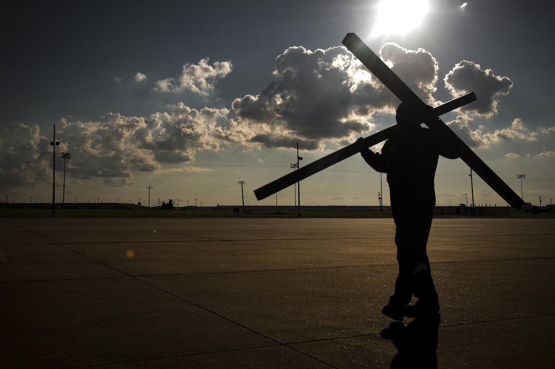 Master Sgt. Mario McBride, 71st Rescue Squadron loadmaster, carries pallet supports across the flightline prior to a sortie in support of Hurricane Harvey relief efforts, Aug. 28, 2017, at Naval Air Station Fort Worth Joint Reserve Base, Texas. The 347th Rescue Group from Moody Air Force Base, Ga. sent aircraft and personnel in support of Air Forces Northern as part of Northern Command's support of FEMA's disaster response efforts. (U.S. Air Force photo by Staff Sgt. Ryan Callaghan)