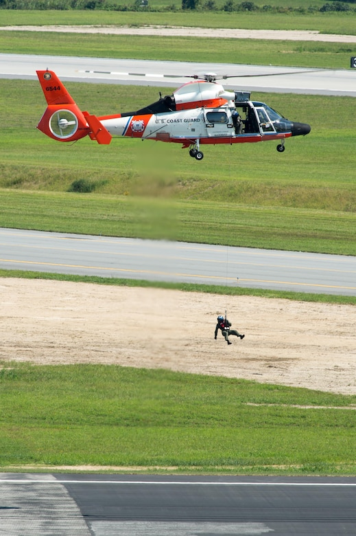 The crew of a U.S. Coast Guard MH-65D Dolphin helicopter performs a search and rescue demonstration at the Thunder Over Dover Open House and Airshow Aug. 26, 2017, at Dover Air Force Base, Del. The open house was a free, two-day event that featured more than 20 aerial demonstrations, static aircraft displays, and other events. (U.S. Air Force photo by Mauricio Campino)