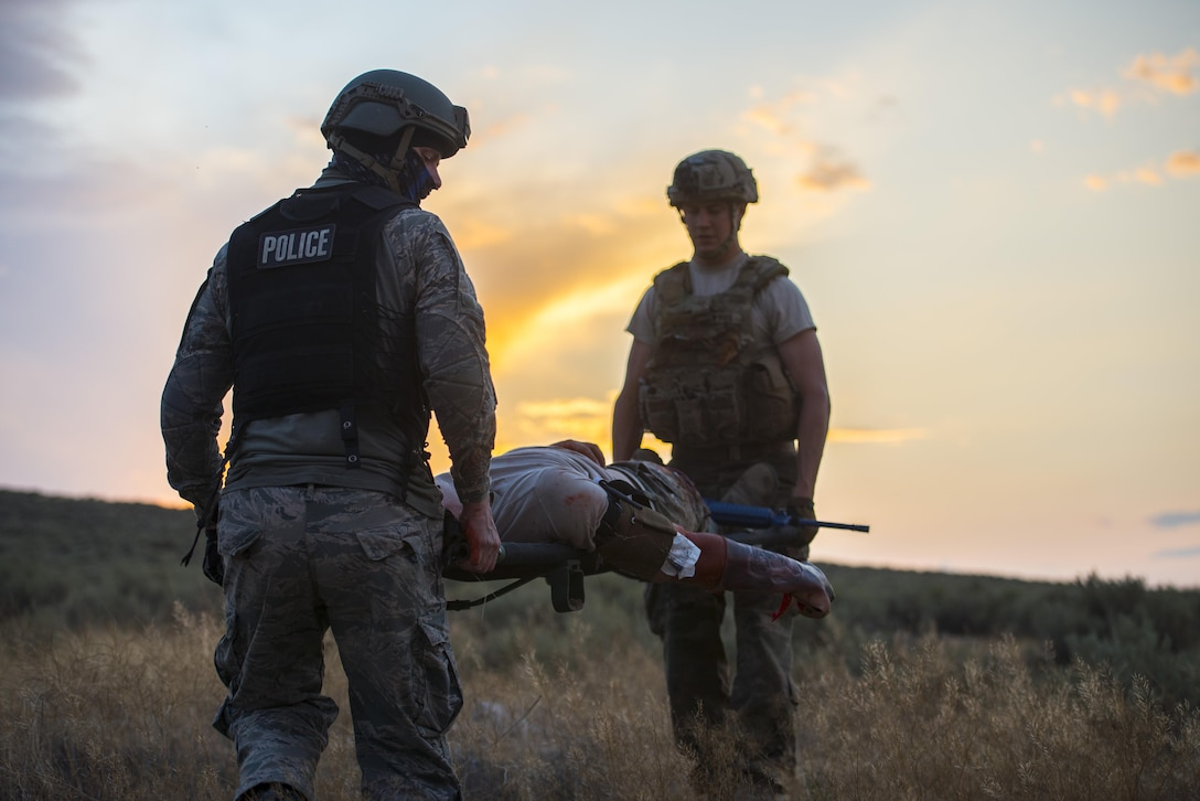 Camerin Hillman, department of the Air Force training instructor and Senior Airman Kelly Kroll, 366th Civil Engineer Squadron explosive ordinance disposal technician transport an injured party during an exercise August 24, 2017, at Orchard training area, Idaho. Civilian contractors and members of the 366th Medical Group attended the exercise and used their experience to improve future training. (U.S. Air Force photo by Airman 1st Class Jeremy D. Wolff/Released)