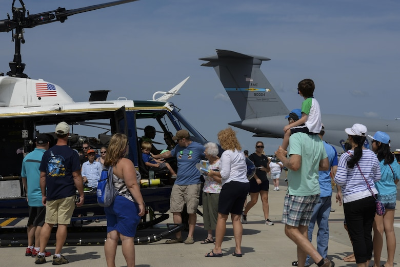 Guests of Team Dover interact with a static display helicopter Aug. 27, 2017, during the Thunder Over Dover Open House on Dover Air Force Base, Del. The open house showcased a spectrum of American air power from World War II to present day. (U.S. Air Force photo by Staff Sgt. Aaron J. Jenne)