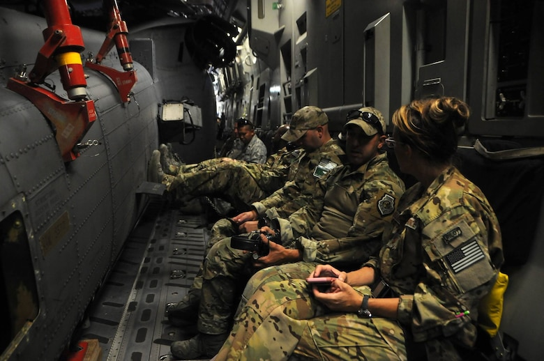 National Guard members sit in a C-17 Globemaster aircraft waiting for take off