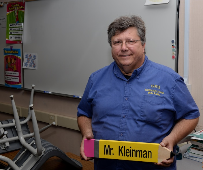 Mark Kleinman, a retired U.S. Air Force lieutenant colonel and a teacher at Travis Elementary School, poses for a photo while holding a pencil with his name on it that was given to him by one of his students at Travis Air Force Base, Calif., Aug. 25. Kleinman taught Airmen how to fly a variety of aircraft during his 33-year Air Force career and now teaches math, English language arts, science and history to 4th grade students. (U.S. Air Force photo by Tech. Sgt. James Hodgman)