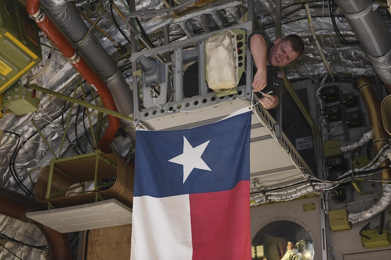 Senior Airman Justin Hampton, 16th Airlift Squadron loadmaster, hangs the state flag of Texas prior to takeoff of a disaster relief mission Aug. 29.