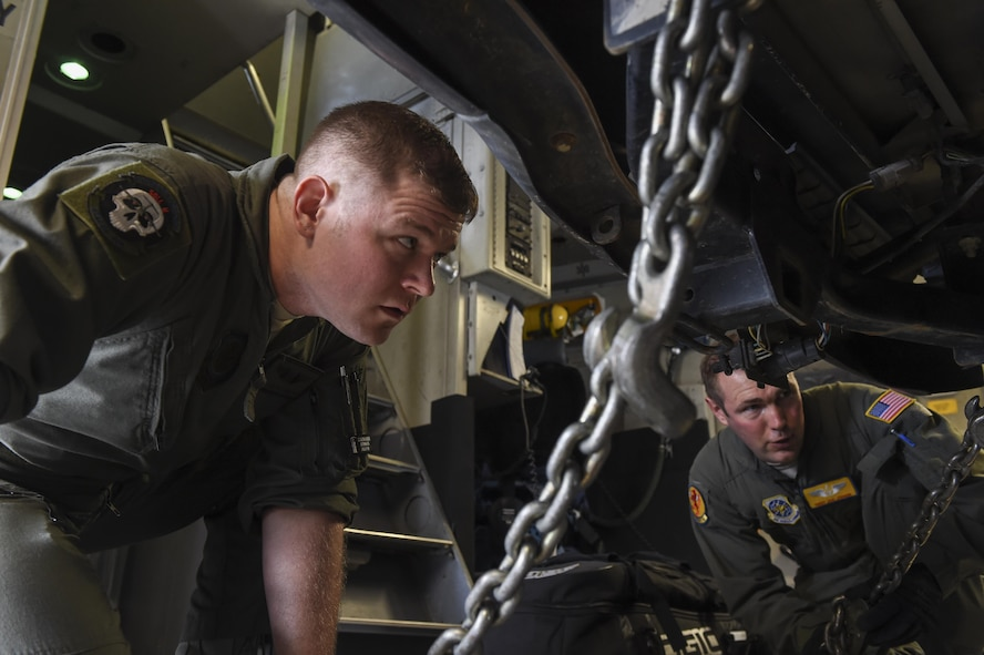 Senior Airman Justin Hampton, left, and Tech. Sgt. Joe Joiner, 16th Airlift Squadron loadmasters, left, checks the winches holding down a vehicle during a cargo on load at Robins Air Force Base, Ga., flightline Aug. 29.