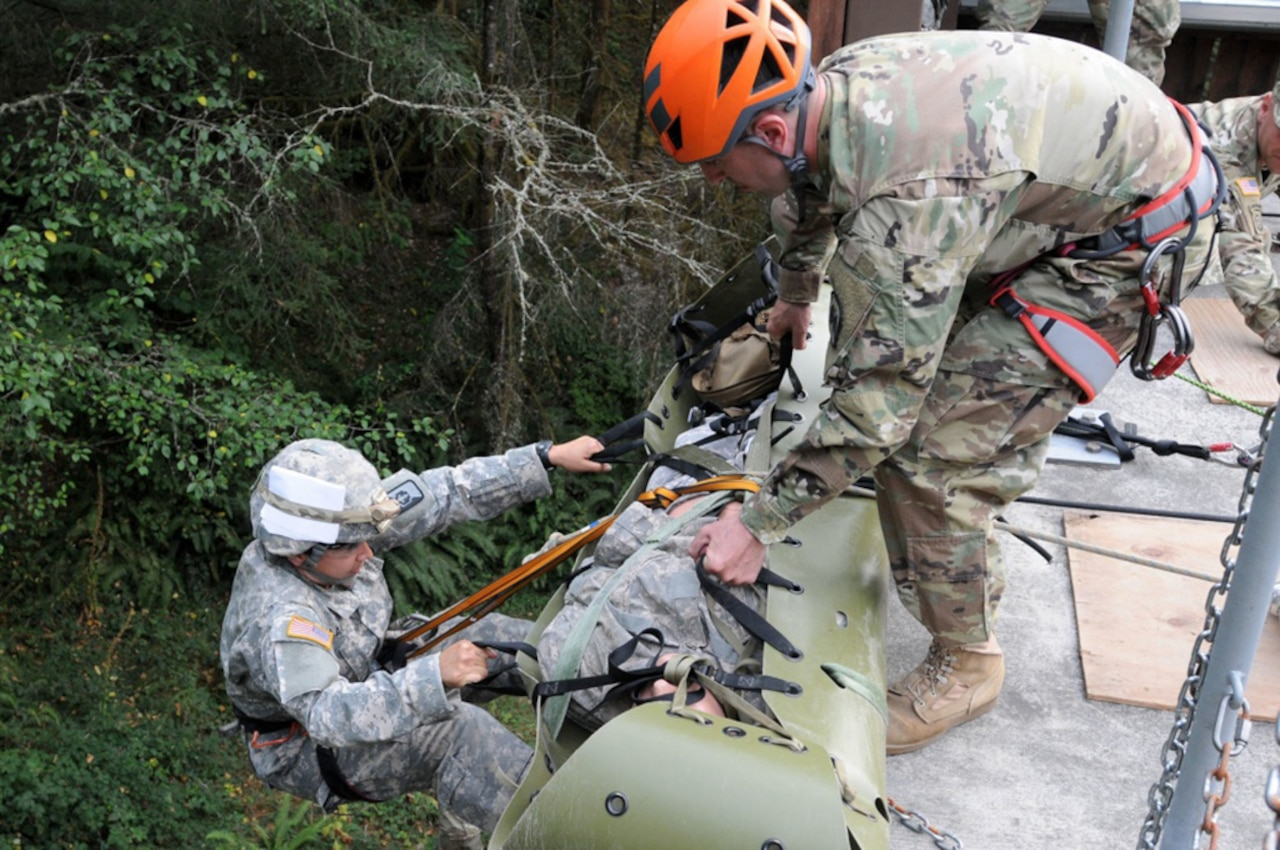 A soldier descends a wall with a simulated casualty.