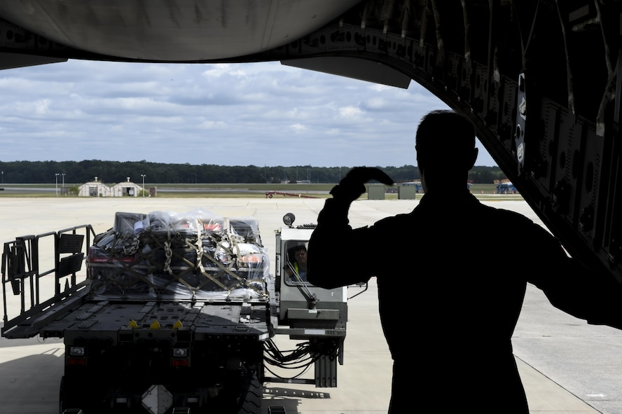 Tech Sgt. Joe Joiner, 16th Airlift Squadron loadmaster, guides a member of the 78th Logistics Readiness Squadron, Robins Air Force Base, Ga., as they load a cargo pallet on to the C-17 Globemaster III at the Robins AFB Aug. 29.