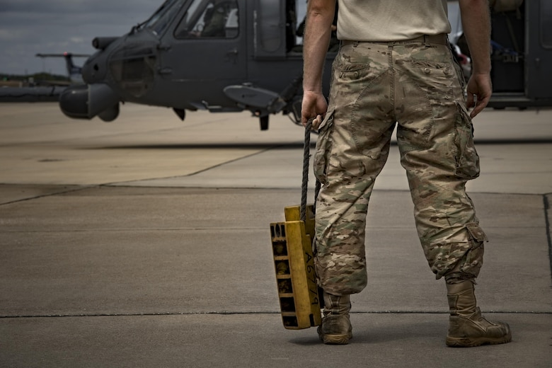 A maintainer from the 41st Helicopter Maintenance Unit waits to bring chocks to an HH-60G Pave Hawk after it completed a sortie in support of Hurricane Harvey relief efforts, Aug. 29, 2017, at Easterwood Airport, College Station, Texas.