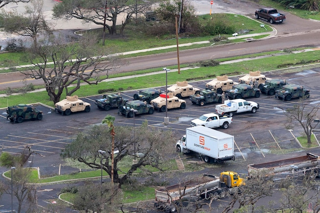 An aerial view shows National Guard vehicles assembled in a parking lot to setting up a collection point for displaced residents.